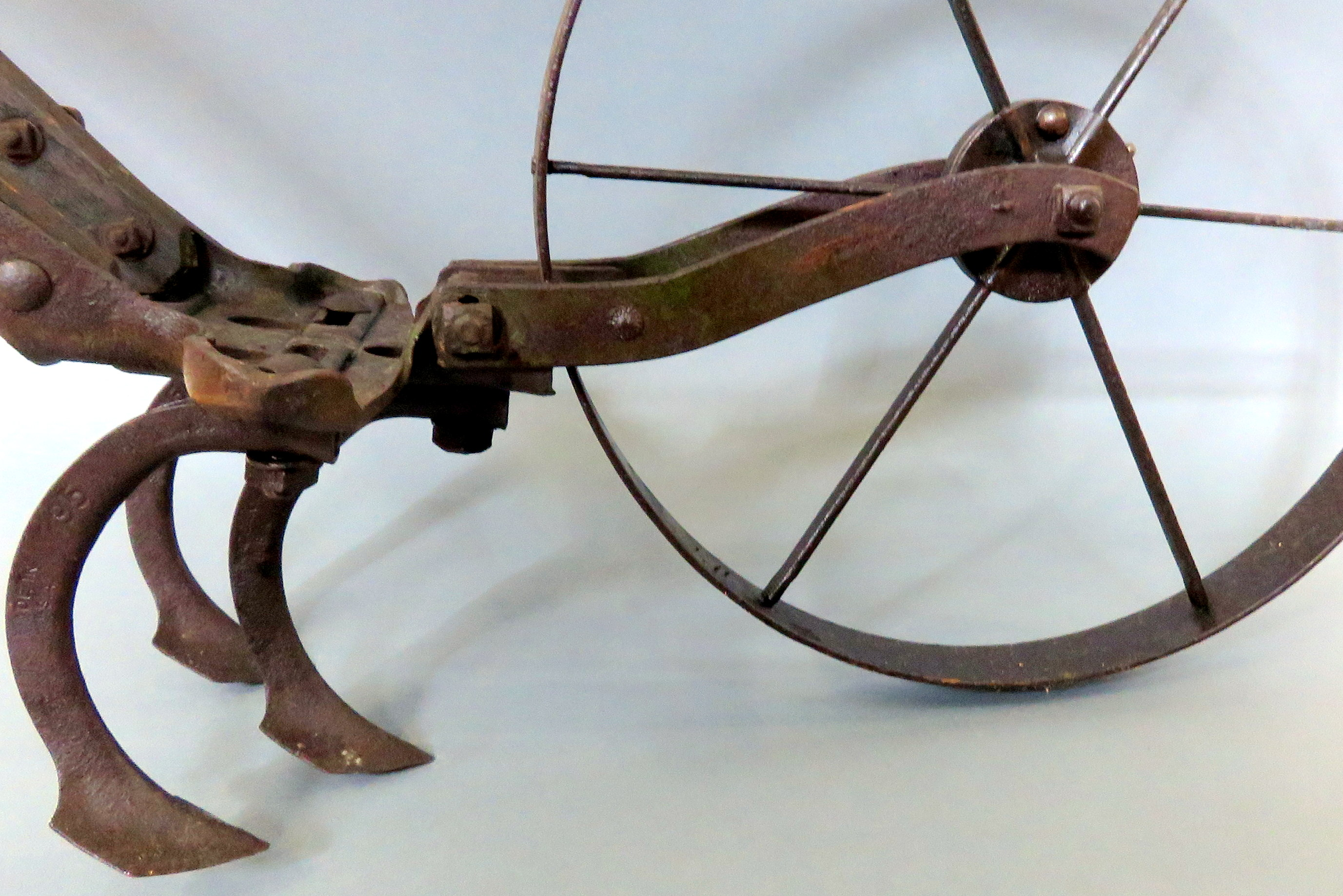 One of the tools with two wheels and two hoe sweeps attached, used for weeding, preparing the soil surface, or creating furrows (rows) as it was pushed by hand.